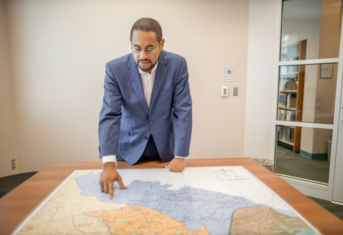 Supervisor Kenny Boddye pointing at a map that is on a table in front of him