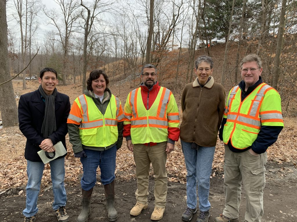 Representatives stand in front of the creek restoration site for a photo