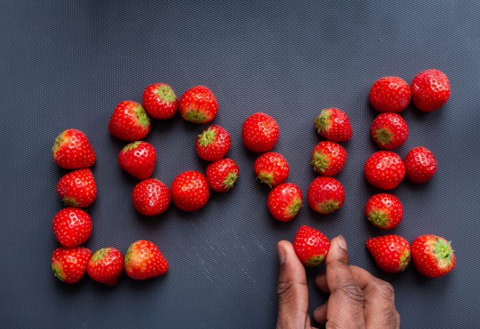 Strawberries on a dark background are arranged to spell out the word love. A hand is placing the last strawberry at the bottom of the V