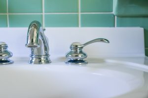 Close up of a sink and a tiled bathroom wall