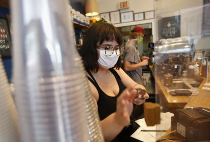 A plates a slice of cake at a counter while wearing a mask
