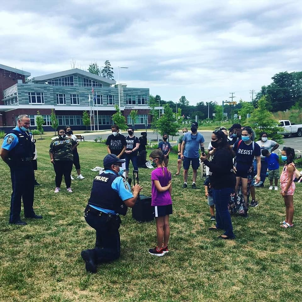 Prince William Police officer kneels to talk to a child at a BLM family protest