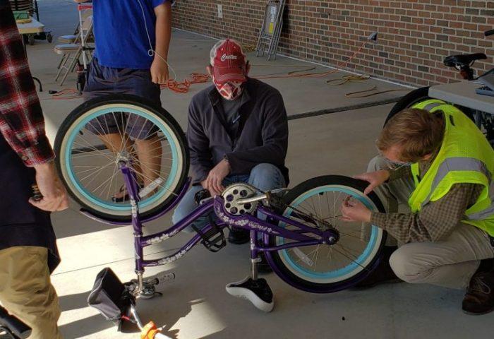 Volunteers repair bike at Fix it fair